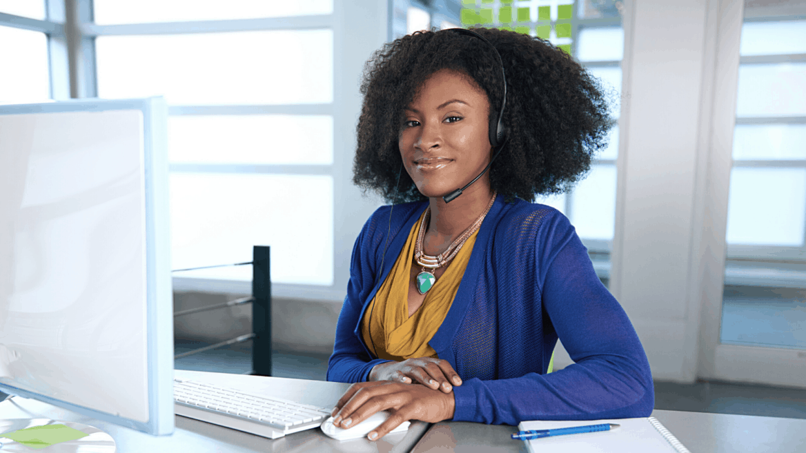 young african american woman working from home in a blue sweater and yellow blouse